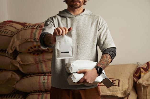 O barista tatuado segura pacotes em branco com grãos de café recém-assados prontos para venda e entrega em cerveja