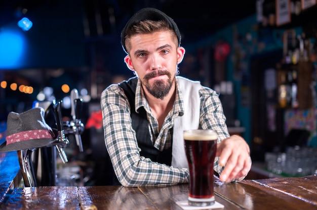 O barman barbudo decora uma mistura colorida enquanto fica perto do balcão do bar em uma boate