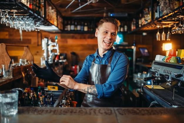 O barman calça luvas de borracha no balcão do bar