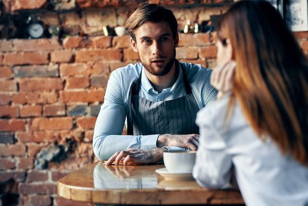 O barman com avental cinza senta-se à mesa e o cliente com uma xícara de café modelo de interior de parede de tijolos
