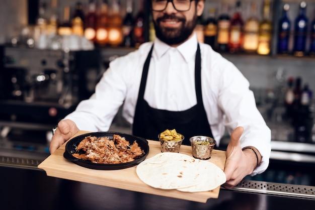 O barman dá comida aos clientes.