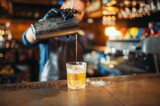 O barman derrama a bebida pela peneira em um copo