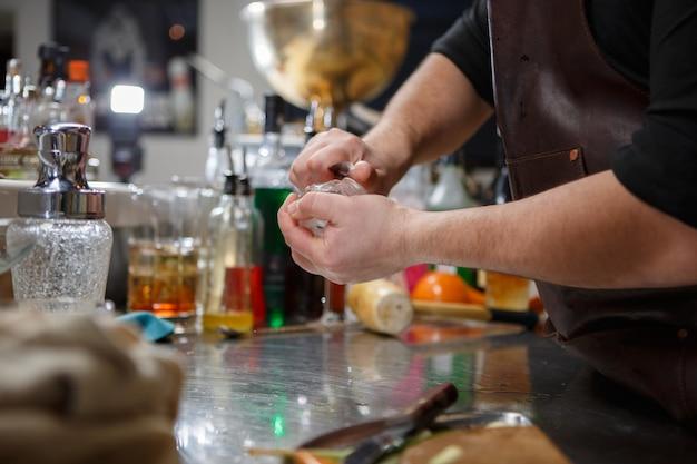 O barman derrama bebida alcoólica em pequenos copos com chamas