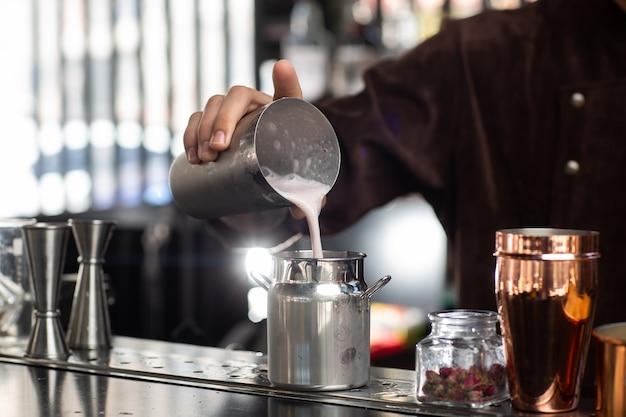 O barman derrama delicadamente o coquetel acabado do shaker de vidro no corpo de vidro metálico do barman