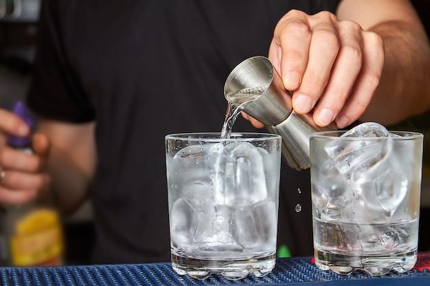 O barman derrama gim em um copo com gelo
