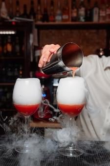 O barman derrama um coquetel vermelho da coqueteleira nos copos, a fumaça sai do coquetel.