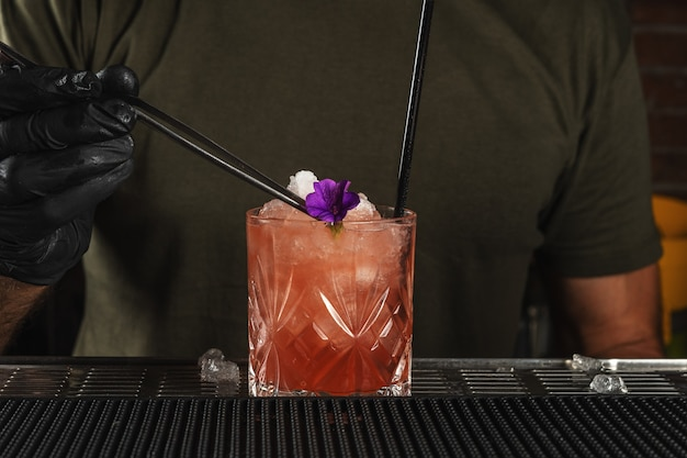 O barman do bar preparando um coquetel alcoólico com gelo e flores