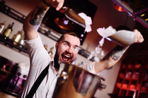 O barman em uma festa em uma boate derrama gelo para coquetéis e grita alegremente contra o bar