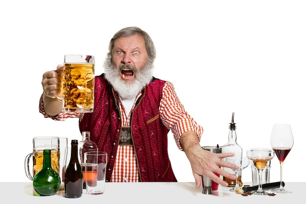 O barman especialista sênior masculino com cerveja no estúdio isolado no fundo branco. dia internacional do barman, bar, álcool, restaurante, cerveja, festa, pub, conceito de celebração do dia de são patrício Foto gratuita