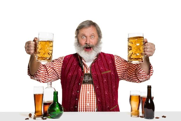 O barman especialista sênior masculino com cerveja no isolado na parede branca. dia internacional do barman, bar, álcool, restaurante, cerveja, festa, pub, conceito de celebração do dia de são patrício
