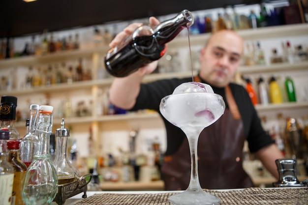 O barman está derramando vinho no copo com gelo gigante, imagem grande angular.