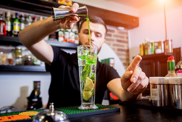 O barman está fazendo um coquetel não alcoólico no balcão do bar. coquetéis frescos. barman no trabalho. restaurante. vida noturna.