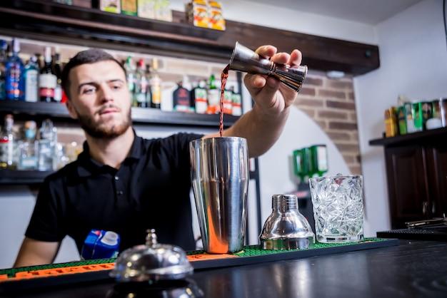 O barman está fazendo um coquetel não alcoólico no balcão do bar. coquetéis frescos. barman no trabalho. vida noturna.