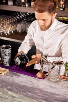 O barman está preparando um coquetel no balcão do bar do lounge