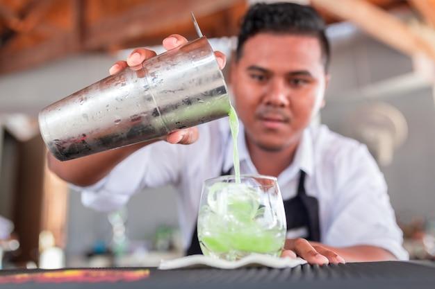 O barman está preparando um coquetel no balcão.