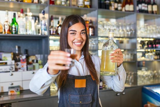 O barman está segurando um copo com bebida alcoólica e uma garrafa na outra mão