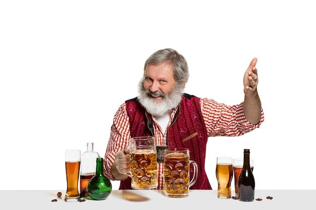O barman experiente sênior com cerveja no estúdio isolado na parede branca
