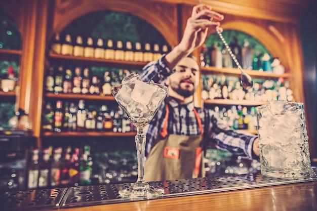 O barman fazendo um coquetel alcoólico no balcão do bar no espaço do bar