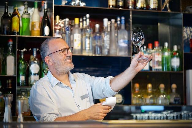 O barman limpa o copo de vinho no trabalho.