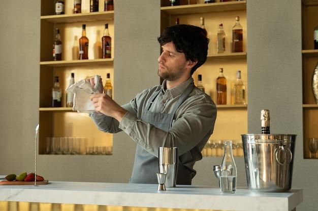 O barman limpa uma taça de martini vazia com um guardanapo limpo