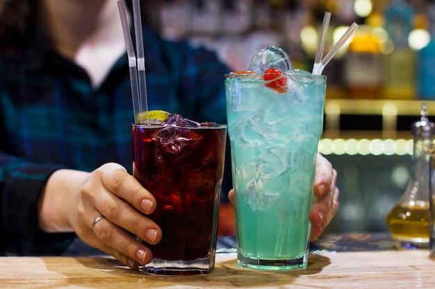O barman menina segurando duas bebidas no bar
