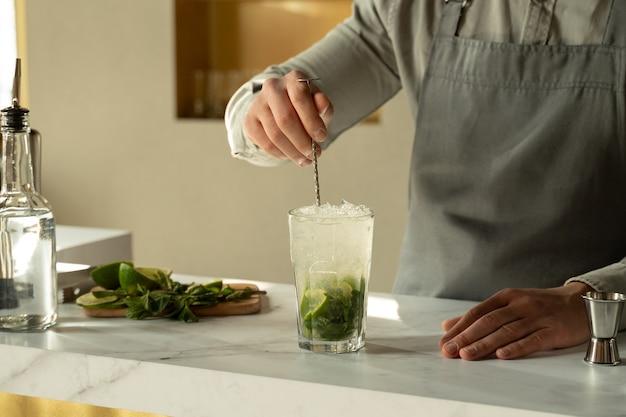 O barman mistura um coquetel de mojito alcoólico com uma colher
