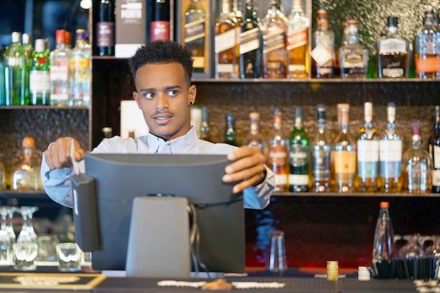 O barman na caixa registradora