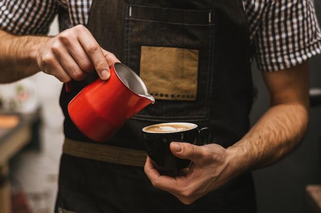 O barman no local de trabalho. barman masculino faz cappuccino.
