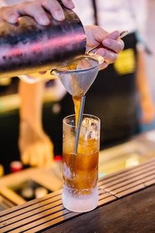 O barman perito está fazendo o cocktail com suco amarelo na discoteca.
