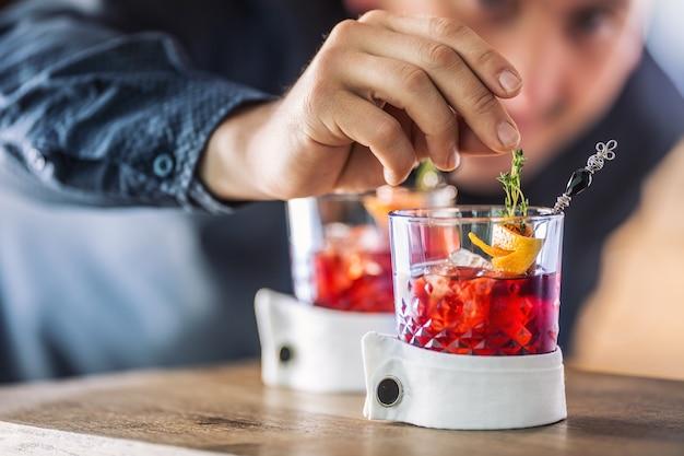 O barman prepara com precisão o coquetel com decoração de frutas e ervas