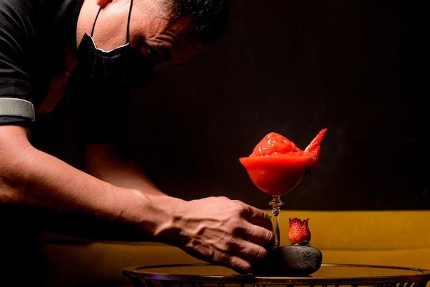 O barman prepara coquetel de daiquiri de morango natural com fundo preto em uma mesa