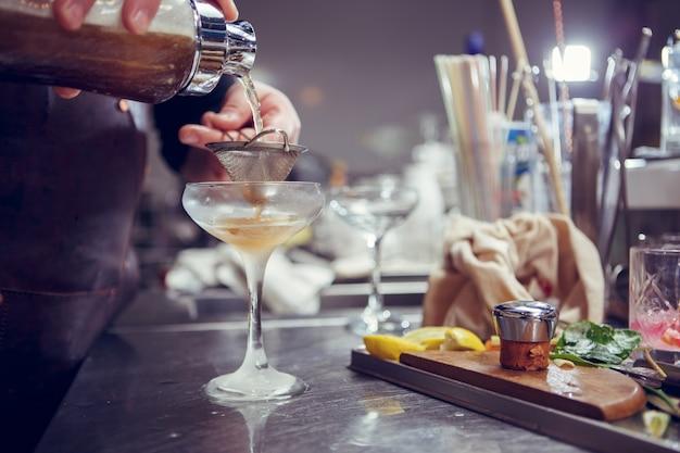 O barman prepara um coquetel atrás de um balcão de bar. imagem tonificada.