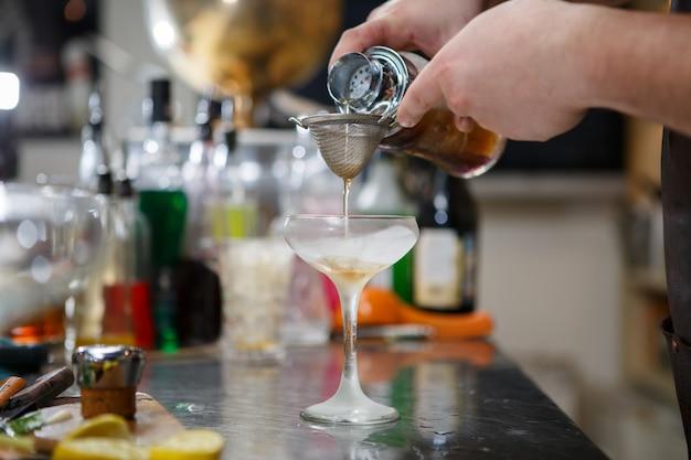O barman prepara um coquetel atrás de um balcão de bar