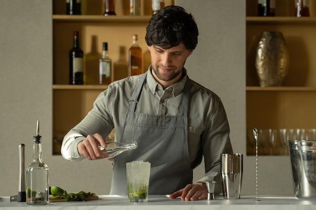 O barman serve refrigerante em um coquetel de mojito e enfeita com limão e hortelã