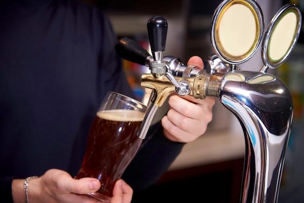 O barman serve uma cerveja em um copo.