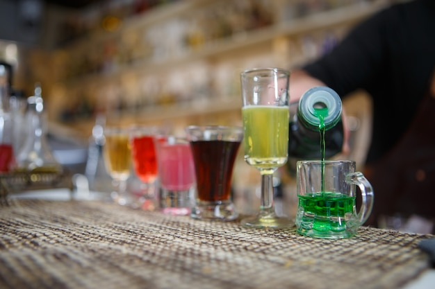 O barman serve vários tipos de bebida alcoólica em pequenos copos no bar