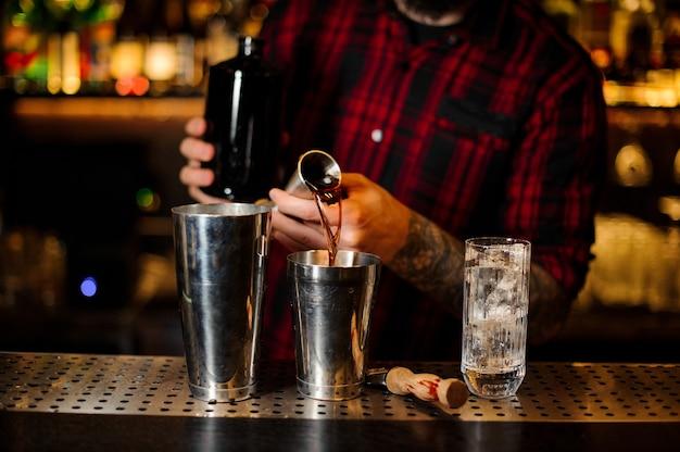 O barman servindo a bebida e fazendo o coquetel da coqueteleira de aço para o shaker de aço no balcão do bar