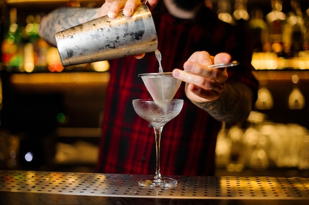O barman servindo um coquetel courpse reviver do shaker de aço no balcão do bar