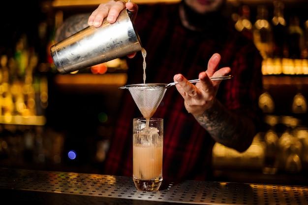 O barman servindo um coquetel singapore sling do shaker de aço através da peneira no balcão do bar