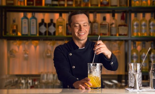 O barman sorridente agita o conteúdo do copo de mistura para preparar um coquetel deslumbrante