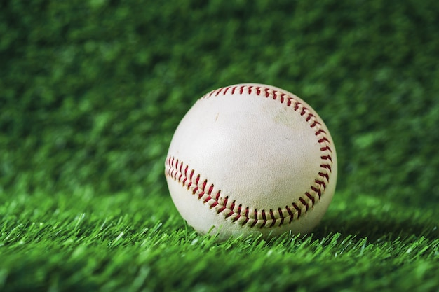 O basebol usado pôs sobre o fundo da grama verde.