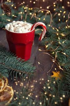 O bastão de doces do fundo do natal ramifica fatias alaranjadas da bebida do chocolate quente no fundo escuro. cartão de férias. vista do topo