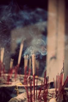 O bastão de incenso em joss, pau pote, foco seletivo no meio incenso com a fumaça