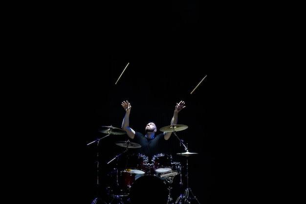 O baterista com um boné e fones de ouvido toca bateria em um show sob uma luz branca em uma fumaça.