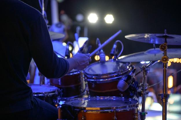 O baterista está tocando bateria no palco do evento