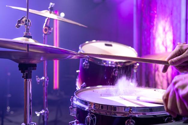 O baterista toca a bateria no estúdio contra um belo fundo de perto.