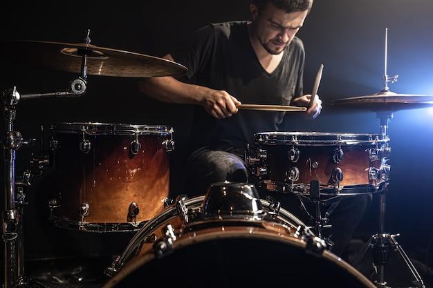 O baterista toca bateria enquanto está sentado na bateria no palco.