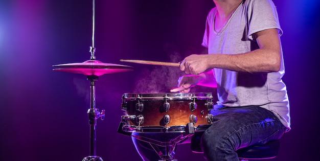 O baterista toca bateria. fundo azul e vermelho bonito, com raios de luz.