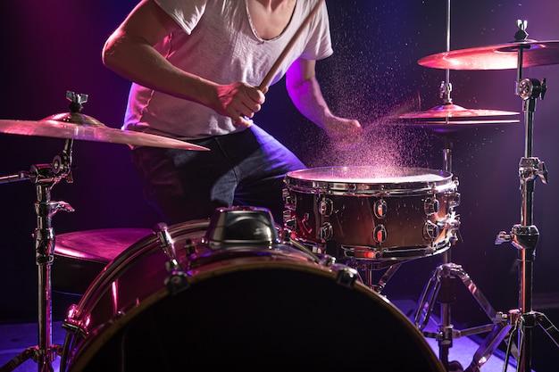 O baterista toca bateria.