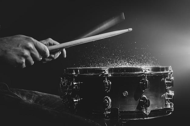O baterista toca com baquetas no tambor, em movimento, monocromático.